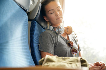 Young woman sleeping peacefully on train