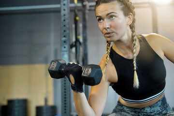 Woman in a gym lifting weights