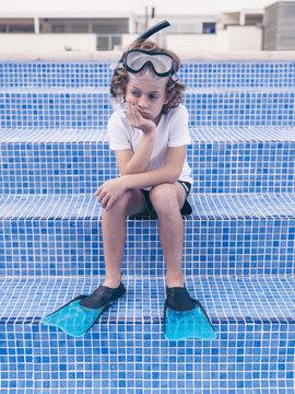 Sad boy in diving equipment n steps of pool