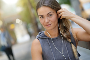 Woman looking serious in relaxed clothing and earbuds