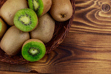 Kiwi fruits in wicker basket on wooden table. Top view