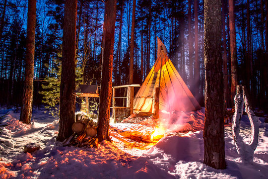 Tipi. Bonfire burns at the home of the Indians. Winter in the forest. Eco tourism. Tipi Indians. The peoples of America. Ethnography. National home of American Indians.