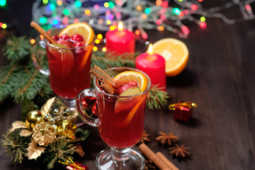 Mulled wine on a wooden background with candles, pine branches and Christmas lights. Selective focus