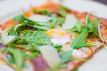 pizza with arugula and quail egg