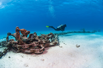 Scuba Diver at an Anchor Chain close to the white sand in clear blue water