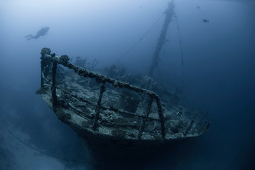 Lonesome scuba diver on a wreck in the dawn in mystical ambiance