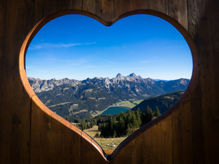 Tannheimer Tal panorama with view on the Haldensee seen through a wooden heart