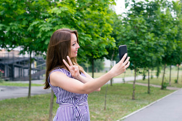 Young female holding phone for picture selfie