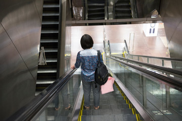 Girl on the escalator in the metro singapore. Lady with a shopping bag down in the waiting room