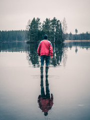 Man is walking on water ice lake. Light is reflected lika a mirror. Small island in background.