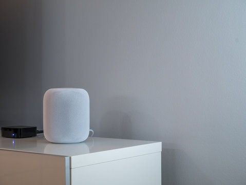 Smart wireless speaker at home to play music. Grey an white background.