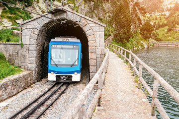 The train leaves the tunnel in the mountains