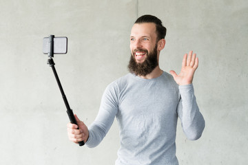 Excited blogger waving at camera. man taking selfie with phone on monopod. online video streaming.