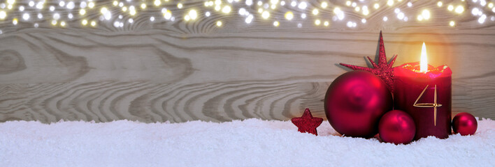 Fourth Advent. Christmas background with candle and red bauble .