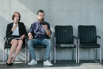 waiting for job interview. woman drinking coffee man using phone. applicants sitting in chairs.