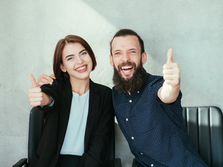 Happy smiling business woman and hipster bearded man showing thumbs up. success and teamwork concept.