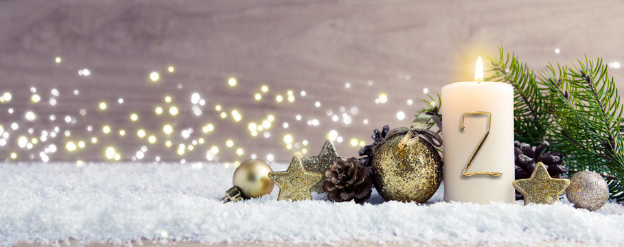 Second Advent. Christmas background with Advent candle and golden decoration.