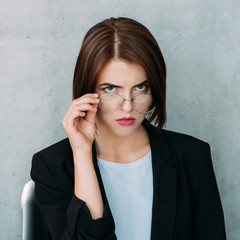 serious grumpy confident business woman looking at camera holding eyeglasses.
