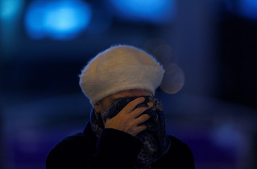 A woman covers her face during a period of fog and air pollution in Skopje