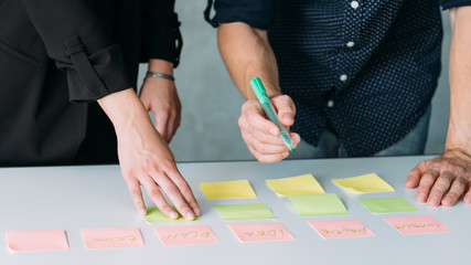 business man and woman working in team writing memos on sticky notes. planning strategy and brainstorming