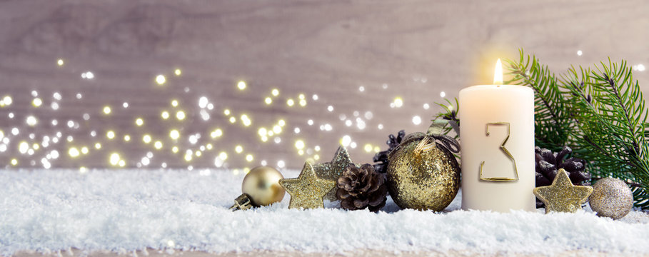 Third Advent.Christmas background with Advent candle and golden decoration.