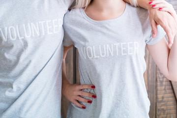 midsection of man and woman wearing casual t-shirts saying Volunteer. social awareness and concern