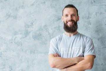 Happy bearded man wearing volunteer t-shirt smiling at camera on gray background. participation altruism and charity