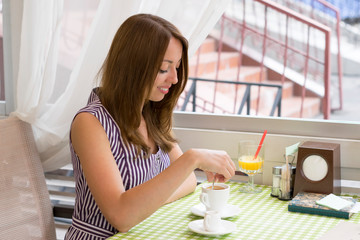 Relaxed happy woman with cup of coffee in cafe