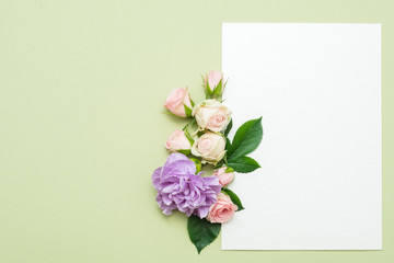empty white paper with bunch flowers on green background. congratulation card mockup