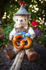 Cute Bavarian Guy at October Season / Smart, adorable teddy bear wearing german bavarian traditional costume leather pants and hat, delicious pretzel with blue ribbon in his hands, sitting at roof, na