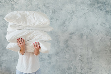 Woman holding big pile of white soft cozy pillows on gray background. bedding and sleeping concept