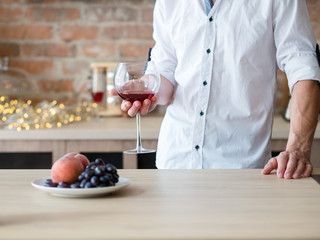 man in white shirt standing at table with glass of red wine. eating habits and gourmet drinking tastes
