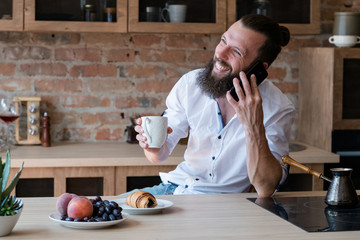 man holding cup of coffee and chatting on phone in kitchen. breakfast and morning leisure