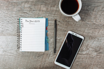 Business concept, blank notepad, smartphone and coffee, on a wooden table,