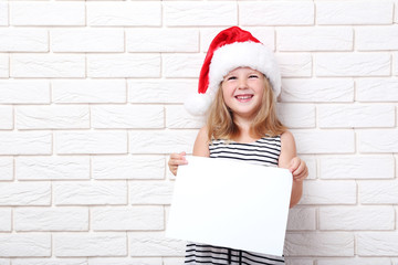 Little girl in santa hat holding blank sheet of paper on brick wall background