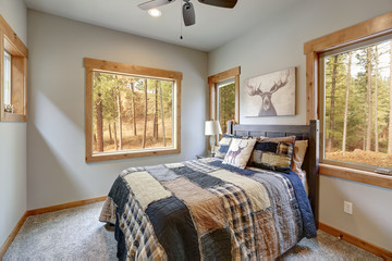 Country style bedroom with wooden bed and lots of windows