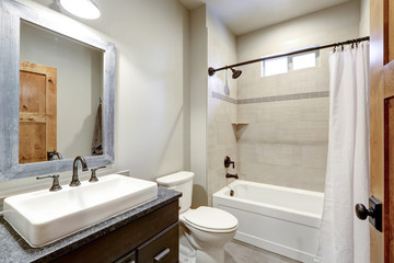 White bathroom interior with a vessel sink and ivory subway tile.