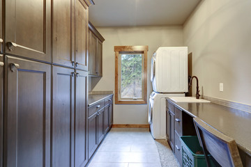 Laundry room with lots of space and floor to ceiling dark cabinets.