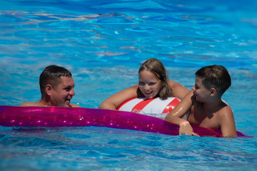 Father and his teenager son and daughter relaxing at the weekend, swimming in a pool on an inflatable pool raft.