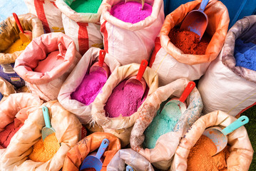 Bright moroccan dry paint in open sacks, dyes powdered pigments, paint of different typical colors for sale. Blue town Chefchaouen, Morocco