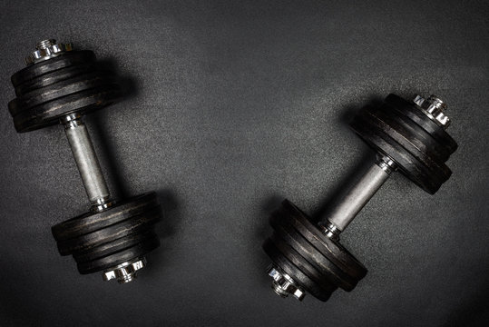 Gym dumbbells on black background with copy sapce, Photograph taken from above