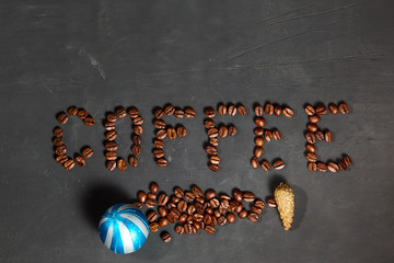 The inscription is laid out coffee beans on a black concrete background