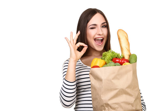 Beautiful woman holding grocery shopping bag on white background