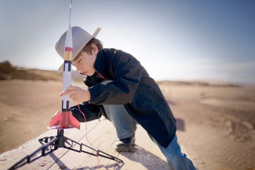 Young boy wearing a hat and putting together a toy rocket at the beach.