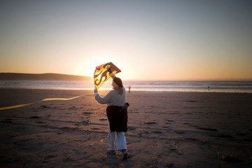 Mid-adult woman holding a kite on the beach at sunset.