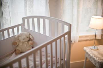 Soft toy in a cot inside an empty nursery.