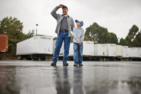 Young boy walking with his father standing in an outdoor freight yard.