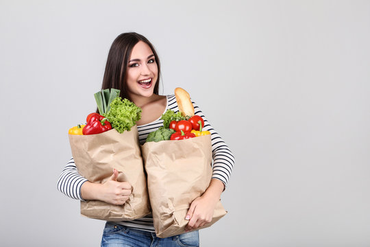 Beautiful woman holding grocery shopping bags on grey background