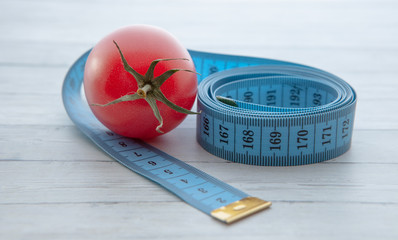 Measuring tape and juicy tomato, the concept of healthy nutrition and weight loss