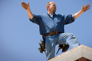 Male builder standing on the roof of a house.